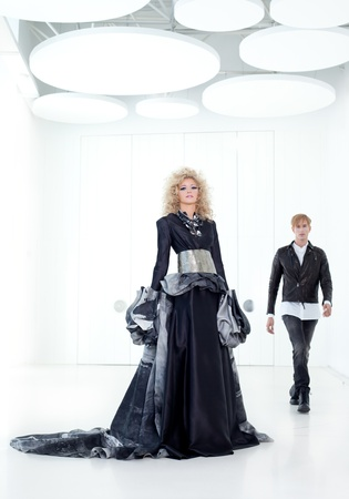 Black haute couture retro futurist couple in modern white hall with vampire inspiration photo