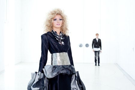 Black haute couture retro futurist couple in modern white hall with vampire inspiration Banque d'images