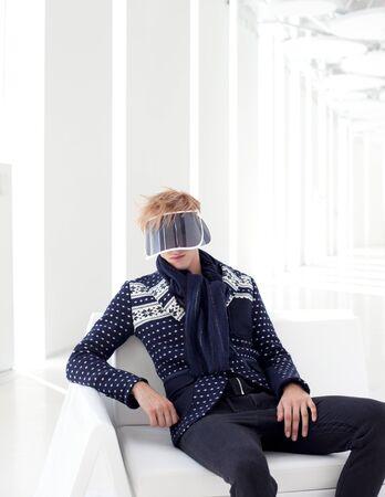 modern male model with futuristic sci-fi visor sitting in white indoor photo