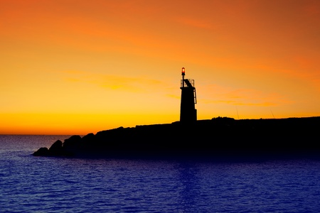 Golden sunrise sunset in sea red beacon lighthouse in Mediterranean Denia Spain photo
