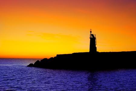 Golden sunrise sunset in sea red beacon lighthouse in Mediterranean Denia Spain photo