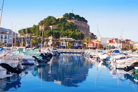 Denia mediterranean port village with castle mountain and blue sea water