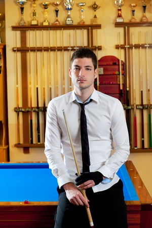Billiard handsome young winner man with shirt tie and cue at trophy club photo