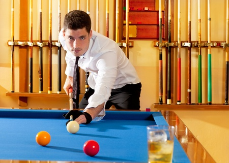cue sports: Billiard winner handsome man playing with cue and balls at club Stock Photo