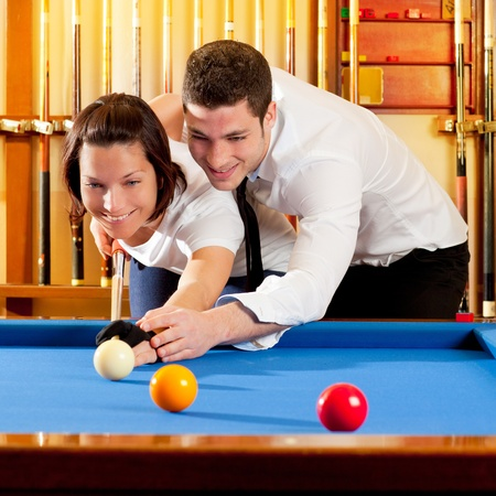 couple playing billiard expertise teacher and beautiful girl photo