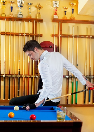 Billiard winner handsome man playing with cue and balls at club photo