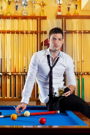 Billiard handsome player man drinking some alcohol in club photo