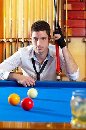 pool table: Billiard expertise man posing on blue with alcohol on the rocks glass