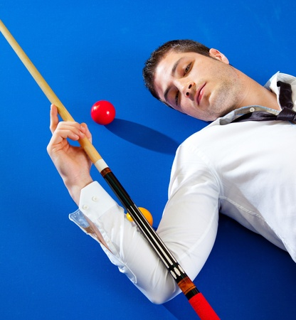 billiard young man player lying on pool blue table with balls Stock Photo - 13123513
