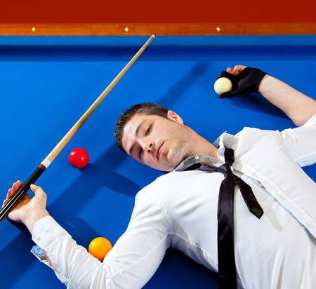 billiard young man player lying on pool blue table with balls Stock Photo - 13123253