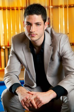 handsome man with suit sitting posing in billiard pool in club photo