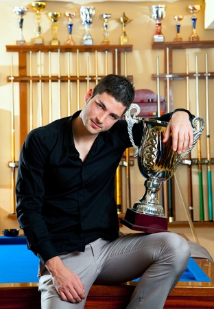 Happy proud winner man with big trophy silver cup in billiard club