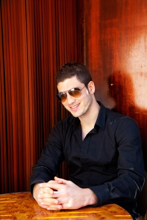 Latin mediterranean handsome man in wooden corner with sunglasses photo