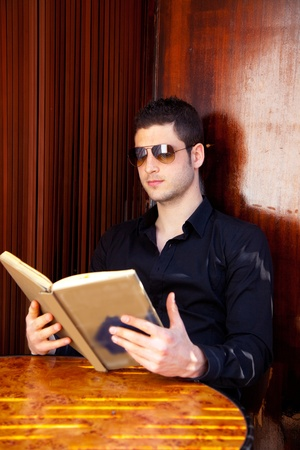 Latin tourist man reading a map book with sunglasses Stock Photo - 13123887