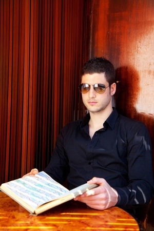 Latin tourist man reading a map book with sunglasses Stock Photo - 13123913