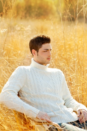 Autumn winter man portrait in outdoor dried grass field with turtleneck sweater photo