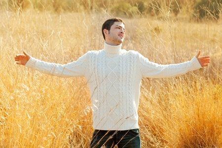 Autumn winter man in outdoor golden grass field with turtleneck sweater open arms photo
