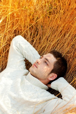 country boy: Autumn winter man portrait lying in golden grass field with turtleneck sweater