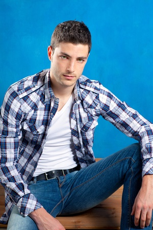 handsome young man with plaid shirt sitting on wood in blue background photo