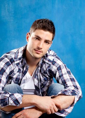 europe closeup: handsome young man with plaid shirt on blue background