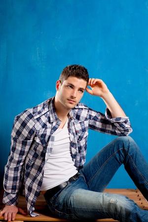 male fashion model: apuesto joven con camisa de cuadros que se sienta en la madera en fondo azul