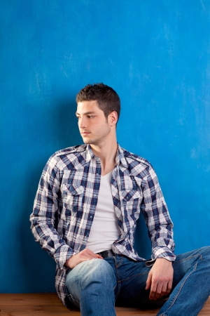 plaid shirt: handsome young man with plaid shirt sitting on wood in blue background