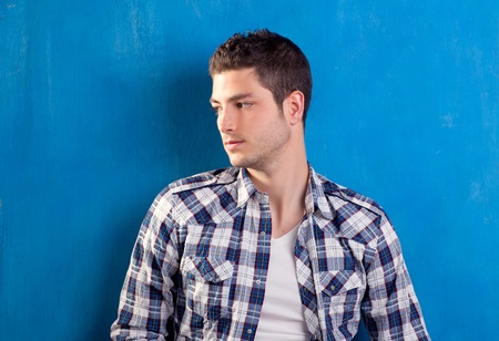 handsome young man with plaid shirt on blue background Stock Photo - 13123835