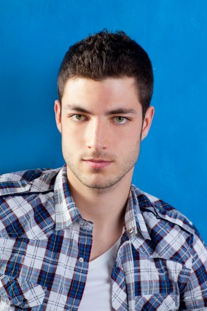 italian PEOPLE: handsome young man with plaid shirt on blue background