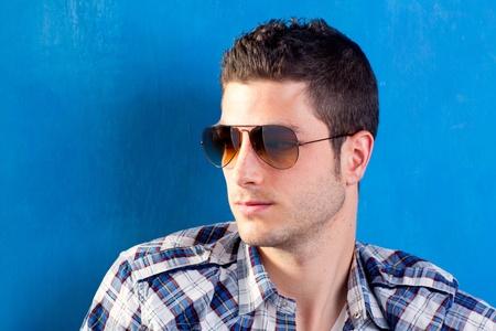 chemise carreaux: beau jeune homme avec chemise � carreaux et lunettes de soleil sur fond bleu Banque d'images