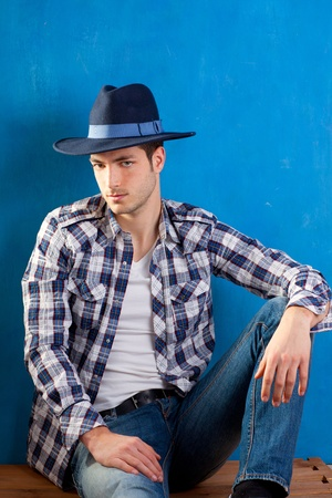 handsome young man with plaid shirt and cowboy hat on blue background photo