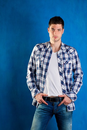 trendy male: handsome young man with plaid shirt denim jeans in blue background Stock Photo