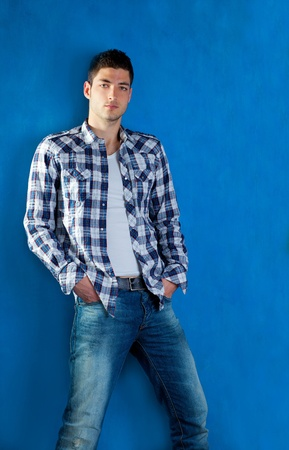belleza masculina: apuesto joven con pantalones a cuadros camisa de mezclilla en color azul de fondo