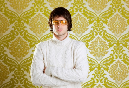 70s adult: retro hip young man with vintage glasses and winter  turtleneck sweater on wallpaper