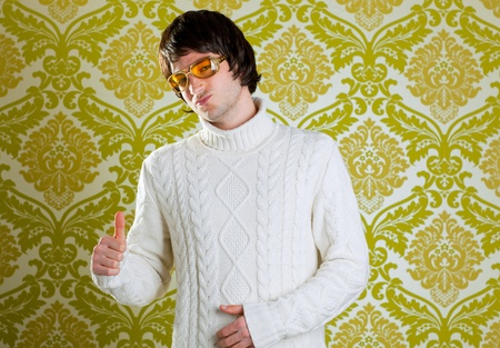 retro hip young man with vintage glasses and winter  turtleneck sweater on wallpaper photo