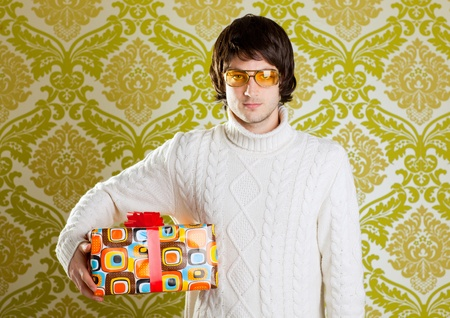 70s adult: retro hip young man glasses holding  psychedelic gift box on wallpaper