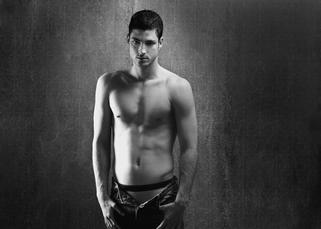 manhood: Black and white sexy young denim shirtless man on retro grunge background