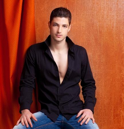 italian man: Latin spanish man portrait open black shirt with curtain and orange vintage background