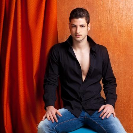 spanish style: Latin spanish man portrait open black shirt with curtain and orange vintage background