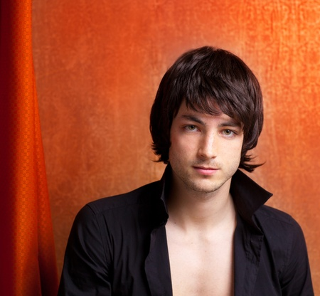 british man: british indie pop rock look young man on orange brown retro background Stock Photo