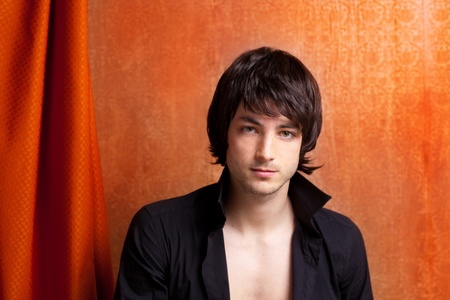 indie: british indie pop rock look young man on orange brown retro background Stock Photo