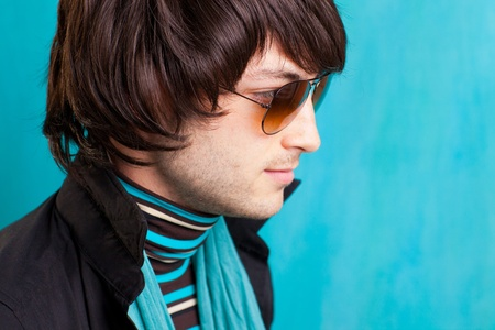 70s adult: british indie pop rock look retro hip young man with sunglasses on blue Stock Photo