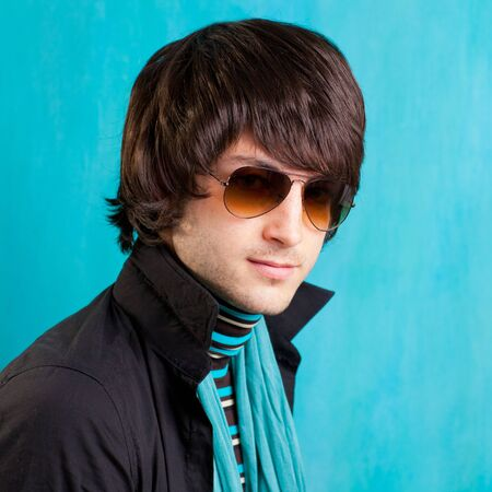 crazy man: british indie pop rock look retro hip young man with sunglasses on blue Stock Photo