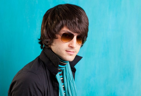british indie pop rock look retro hip young man with sunglasses on blue photo