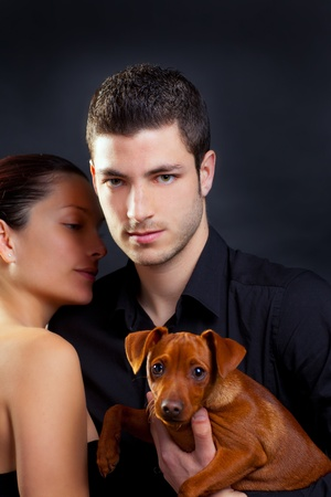 Couple in love with brown little pet puppy dog mini pinscher  photo