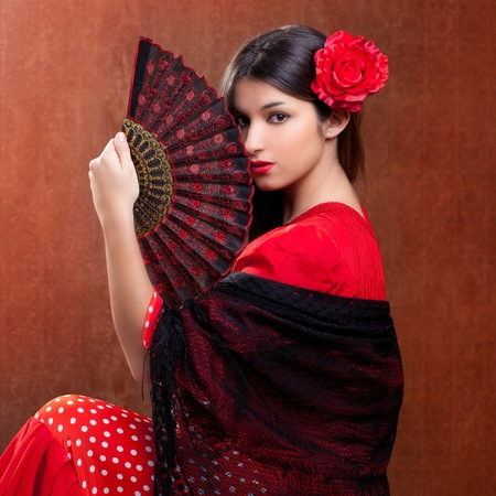Gipsy flamenco dancer Spain girl with red rose and spanish hand fan photo