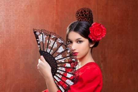 Gypsy flamenco dancer Spain girl with red rose spanish hand fan and peineta comb photo