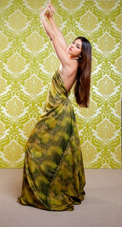 Asian Indian woman dancing full length with ethnic dress on green wallpaper photo