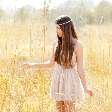yellow dress: Asian indian woman walking in golden dried grass field Stock Photo