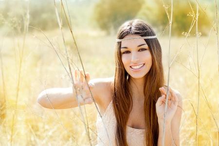 Asian indian woman portrait in golden dried grass field photo