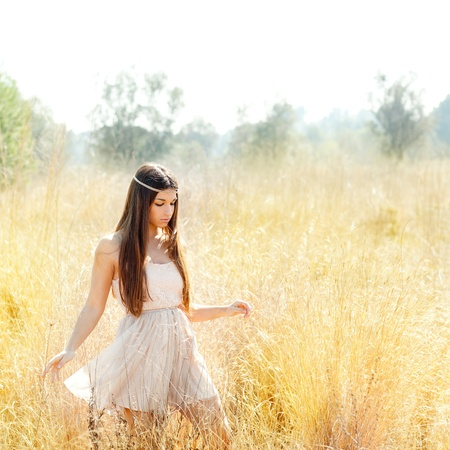 adult indian: Asian indian woman walking in golden dried grass field Stock Photo